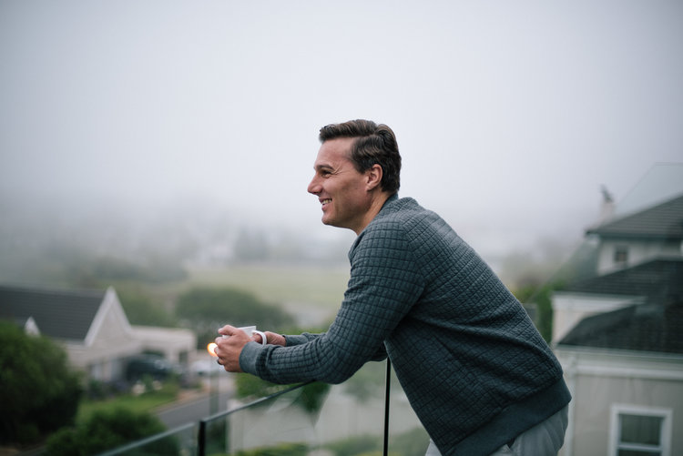 Hein standing on a balcony with the city in the background on a foggy morning
